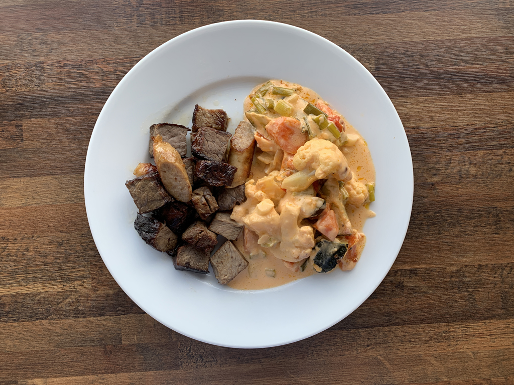 a plate with baked vegetables in cheese sauce and warmed up steak pieces